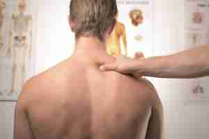 Man seated facing away whilst having his right trapezius massage palpated. Anatomy posters in the background.